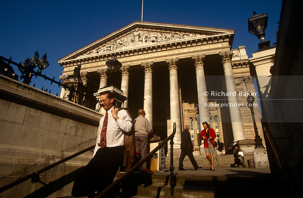 A gentleman carrying his jacket over a shoulder descends the steps from the bright daylight to the darkness of the London Underground, before making his way home from Royal Exchange at Bank Triangle by tube. Behind him are the tall and solid Corinthian pillars of the 3rd Royal Exchange built in 1842 by Sir William Tite in a wide area known as Bank Triangle which is adjacent to the Bank of England in the heart of the capital's financial district known as the Square Mile.