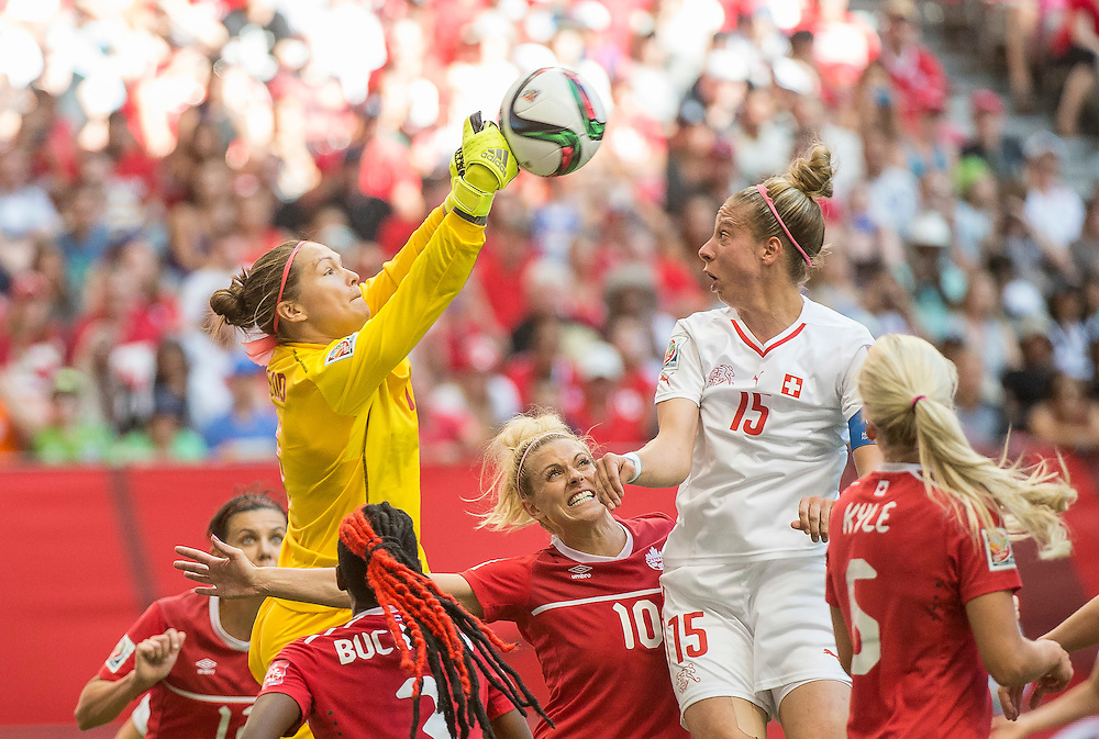 Goalkeeper Erin McLeod of team Canada (yellow jersey) punches the ball over Lauren Sesselman of team Canada (#10) and Caroline Abbe of team Switzerland (#15) in 2015 women's World Cup Soccer in Vancouver during second round action between Canada and Switzerland