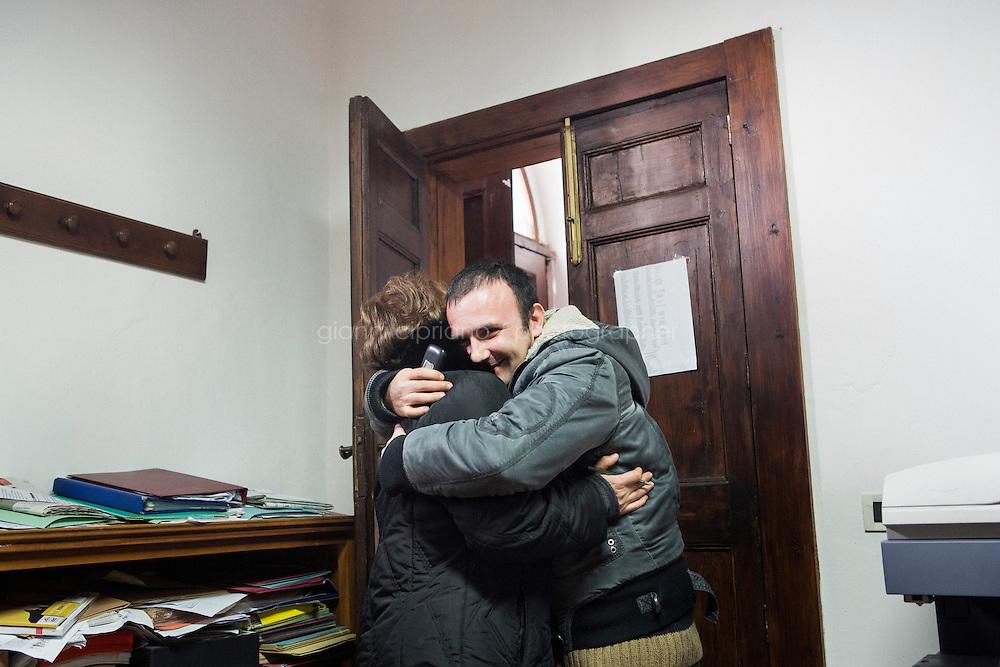 BARCELLONE POZZO DI GOTTO (ME), ITALIA - 20 FEBBRAIO 2015: Natale Miceli (34 anni), un ospite della Casa di Solidarietà e di Accoglienza, abbraccia Carmelina Fugazzotto, operatrice responsabile della comunità, nell'ufficio di Don Pippo Insana  a Barcellona Pozzo di Gotto il 20 febbraio 2015.