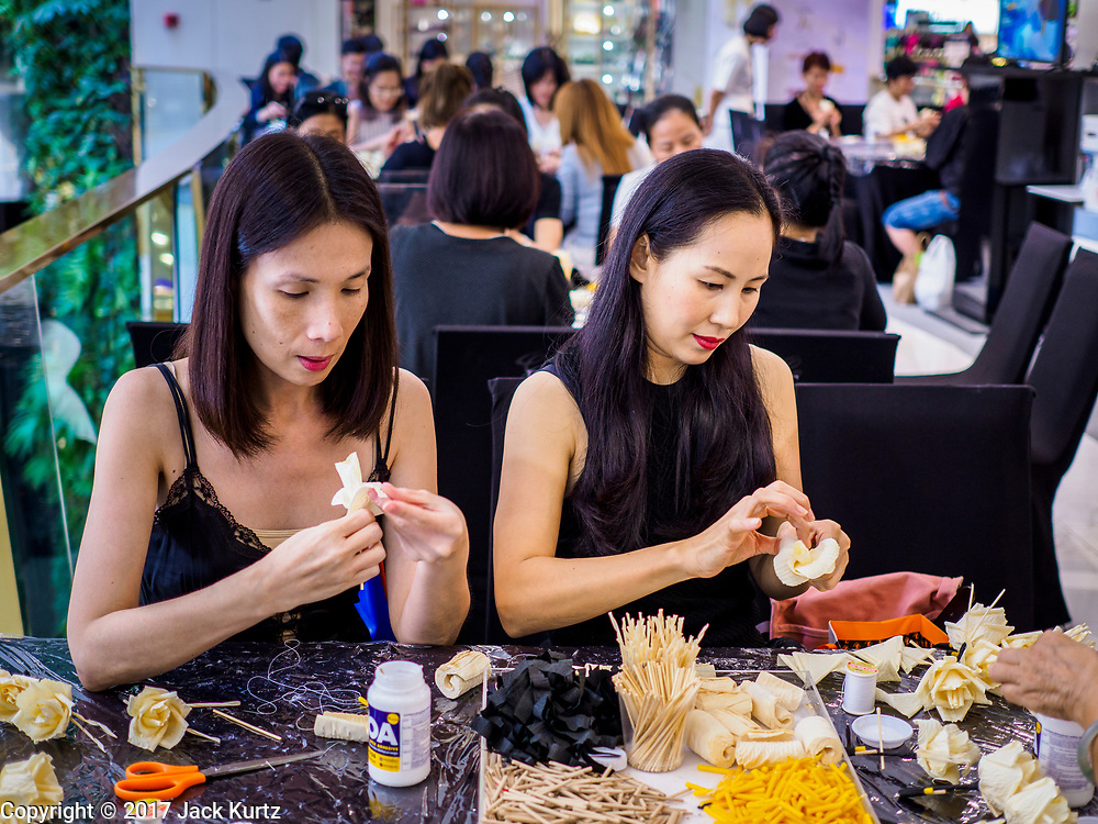 "24 MAY 2017 - BANGKOK, THAILAND: Women at the Emporium, an upscale shopping mall in Bangkok, look at the wooden roses they're making for the cremation of Bhumibol Adulyadej, the Late King of Thailand. In Thai culture it is customary to place wooden flowers in front of a deceased person's coffin or urn as a last tribute before cremation. The Royal Cremation Organisation Committee, which is overseeing plans for the cremation of Bhumibol Adulyadej, the Late King of Thailand, asked the Bangkok Metropolitan Administration (BMA) to provide three million wooden flowers for the late King's cremation. The BMA, in turn, has asked malls and civic organizations to provide flowers. The Mall Group, which owns Emporium, has pledged to provide up to one million wooden ""Wiangping"" roses, which in Thai culture symbolize unconditional love. The late King will be cremated October 26, 2017.     PHOTO BY JACK KURTZ"