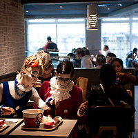 London, UK - 24 October 2013: Ekaterina Voevodkina (L) helps Pavel Ivanov (R) to find his ketchup while having lunch in a KFC restaurant near Piccadilly.