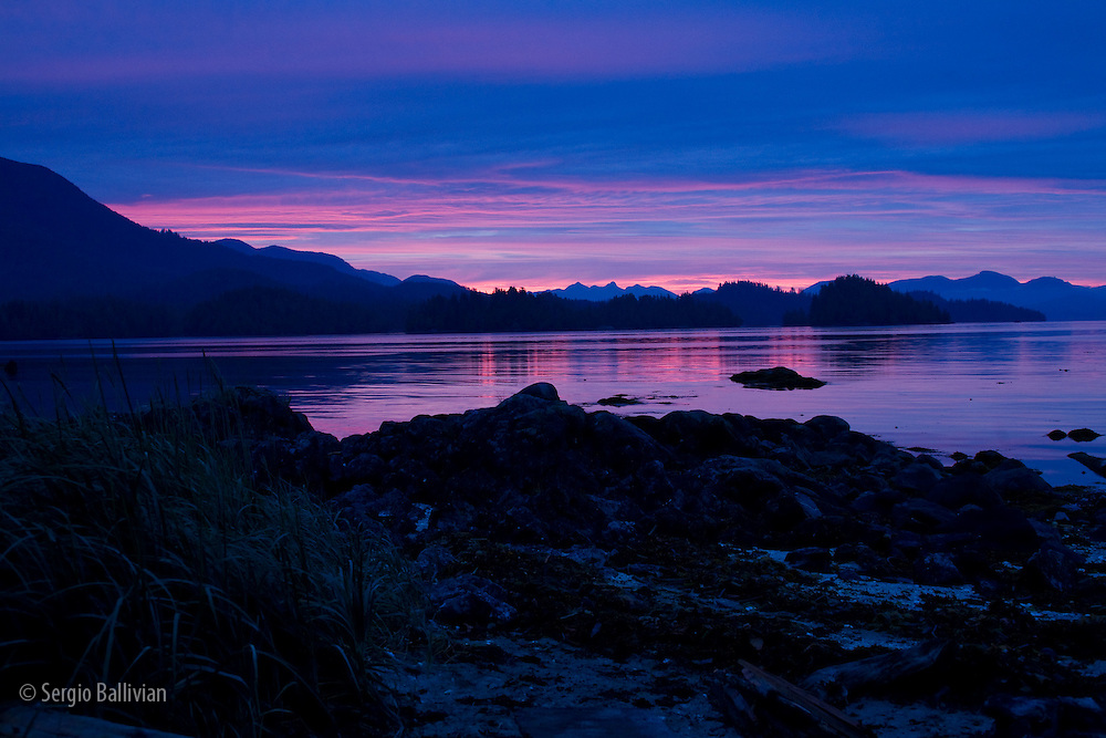The blue and purple colors of pre-dawn light show off calm waters and rugged mountains in Barkley Sound, Vancouver Island, BC.