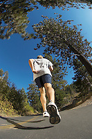 Man jogging down road back view