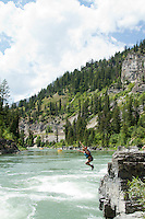 "Young woman jumping into the water near ""Lunch Counter Rapid"" (class 3) on the Snake River near Jackson,  Wyoming."