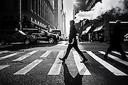 A passerby crosses a street with its head aligned with the fume of a water pipe, NYC