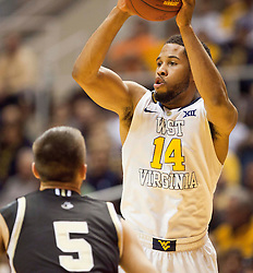 West Virginia Mountaineers guard Gary Browne (14) passes to a teammate against the Wofford terriers during the first half at the WVU Coliseum.