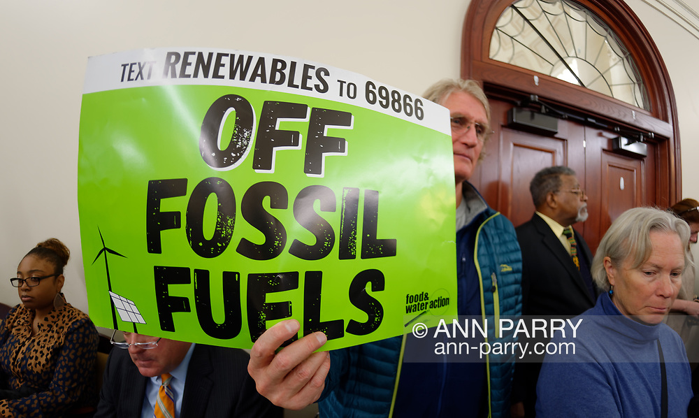 Mineola, New York, USA. 15th Feb, 2019. PHILIP MARINELLI, Huntington, is holding a green sign with Text Renewable to 69866 OFF FOSSIL FUELS on it, by food and water action, during NYS Senate Public Hearing on Climate, Community & Protection Act Bill S7253, sponsored by Sen. Kaminsky, Chair of Senate Standing Committee on Environmental Conservation. This 3rd public hearing on bill to fight climate change was on Long Island.