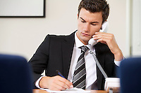 Businessman conversing on landline phone while writing on paper