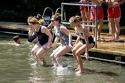 © Licensed to London News Pictures. 07/05/2018. London, UK. Kerry Costello, Suzie Girling and Miriam Harris swim in Hampstead Heath Mixed Bathing Pond in north London as temperatures hit 28C on the hottest May bank holiday since 1999 on Monday, May 7, 2018. Photo credit: Tolga Akmen/LNP