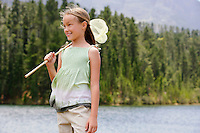 Girl (7-9) standing by lake holding butterfly net.