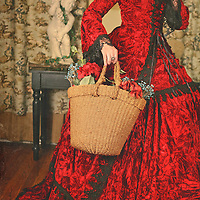 Cropped mysterious shot of a young woman with short black hair and red lipstick wearing a fancy regency red historical gown carrying a woven basket with flowers