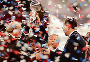 New England Patriots owner Robert Kraft holds the Lombardi Trophy high in the air as confetti flies and television announcer Terry Bradshaw (left) and NFL Commissioner Paul Tagliabue look on after winning the 2002 NFL Super Bowl XXXVI playoff football game against the St. Louis Rams on Sunday, Feb. 3, 2002 in New Orleans. The Patriots won the game 20-17. (©Paul Anthony Spinelli)