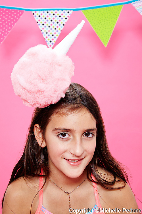 Portrait of Tween girl with long brown hair wearing cotton candy hat against pink seamless.<br /> Photographed at Photoville Photo Booth September 20, 2015