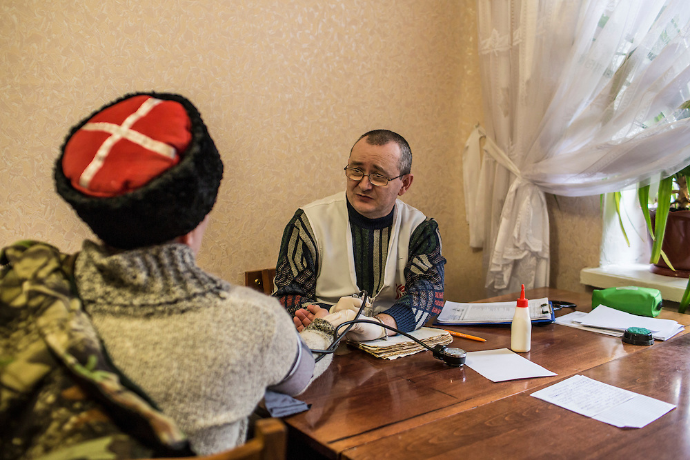 ZIMOGORYE, UKRAINE - MARCH 15, 2015: Andriy Polyakov, right, a doctor with Medecins Sans Frontieres, consults with a patient at the Zimogoryivskaya Ambulatory in Zimogorye, Ukraine. CREDIT: Brendan Hoffman for The New York Times