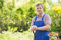 Portrait of confident gardener holding spade in plant nursery