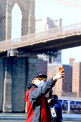 Tourists with face mask front of the Brooklyn Bridge on saturday afternoon in New York, NY on March 14, 2020. As of Saturday morning, New York State had 524 confirmed coronavirus cases.<br /> Photo by Dylan Travis/ABACAPRESS.COM