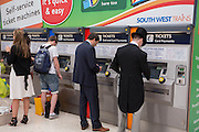 ASCOT RACEGOERS BUYING TICKETS FROM THE AUTOMATED TICKET MACHINE, Royal Ascot racegoers at Waterloo station. London. 21 June 2013.