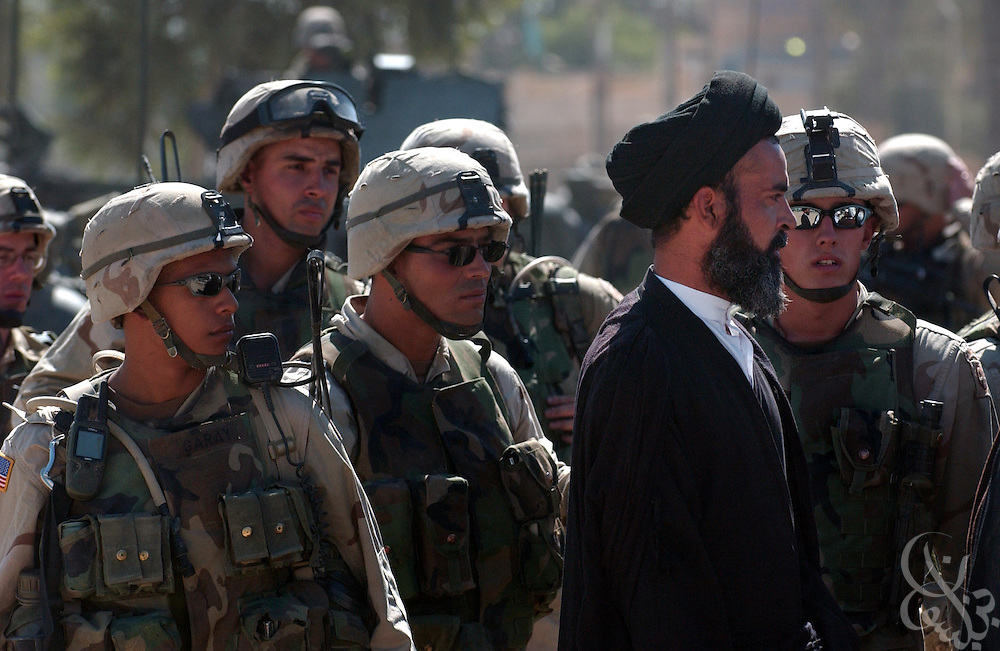 U.S. Army soldiers gather around a local Iraqi Shia cleric October 07, 2003 as they negotiate with leaders of a protest against the detention of local Shia Imam Mo'ayed al-Khezragi by U.S. military  at the al-Baya'a mosque in Baghdad, Iraq.