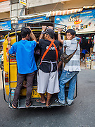 "03 APRIL 2015 - CHIANG MAI, CHIANG MAI, THAILAND: Men standing in the back of a ""songthaew"" in the market in Chiang Mai, Thailand. A songthaew is pickup truck converted to use as a bus common in Thailand. Songthaew is a literal translation of ""two seats"" because two bench seats are installed in the bed of the pickup.      PHOTO BY JACK KURTZ"