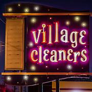 Village Cleaners illuminated in neon