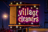 Village Cleaners illuminated in neon