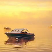Three small boats on their moorings at dawn on Damariscotta Lake. Jefferson, Maine