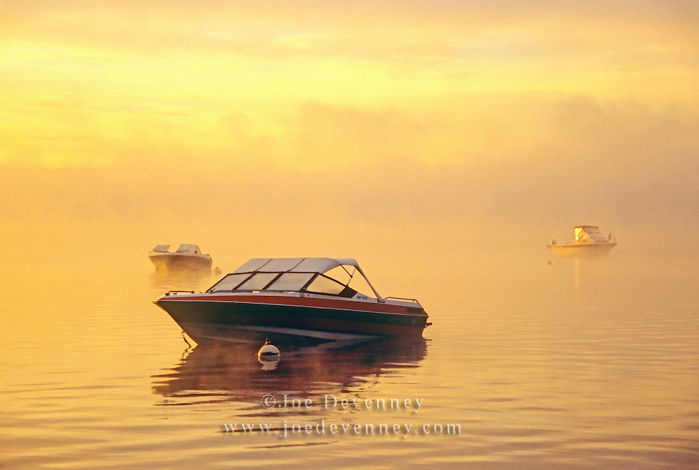Three small boats on their moorings at dawn on Damariscotta Lake. Jefferson, Maine