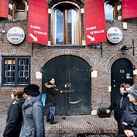 Nederland, Amsterdam , 2 december 2011..Toeristen wandelen voorbij een pand met borden Kamerverhuur voor prostituees op Achterzijds achterburgwal nr 52..n.b. vrouw in het midden is geen prostituee..Foto:Jean-Pierre Jans