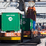 Nederland Zuid-Holland Rotterdam  27-08-2009 20090827 Foto: David Rozing .Serie over logistieke sector.ECT Delta terminal in de haven van Rotterdam. Robotgestuurde wagens vervoeren de containers op de terminal. Onbemande wagens in de rij bij de hijskranen, deze tillen de containers op het zeeschip. .ECT,European Container Terminals, at the Port of Rotterdam. Europe's biggest and most advanced container terminal operator, handling close to three- quarters of all containers passing through the Port of Rotterdam. ECT is a member of the Hutchison Port Holdings group (HPH), the world biggest container stevedore with terminals on every Continent. At the ECT Delta Terminal unmanned, automated guided vehicles  so called AGVs  transport the containers between ship and stack. In the stack, unmanned automated stacking cranes ( ASCs ) ensure that the containers are always stacked in the correct place. Terminal operations are highly automated for discharging and loading large volumes...Holland, The Netherlands, dutch, Pays Bas, Europe .Foto: David Rozing