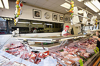 Butcher with processed meat in display case