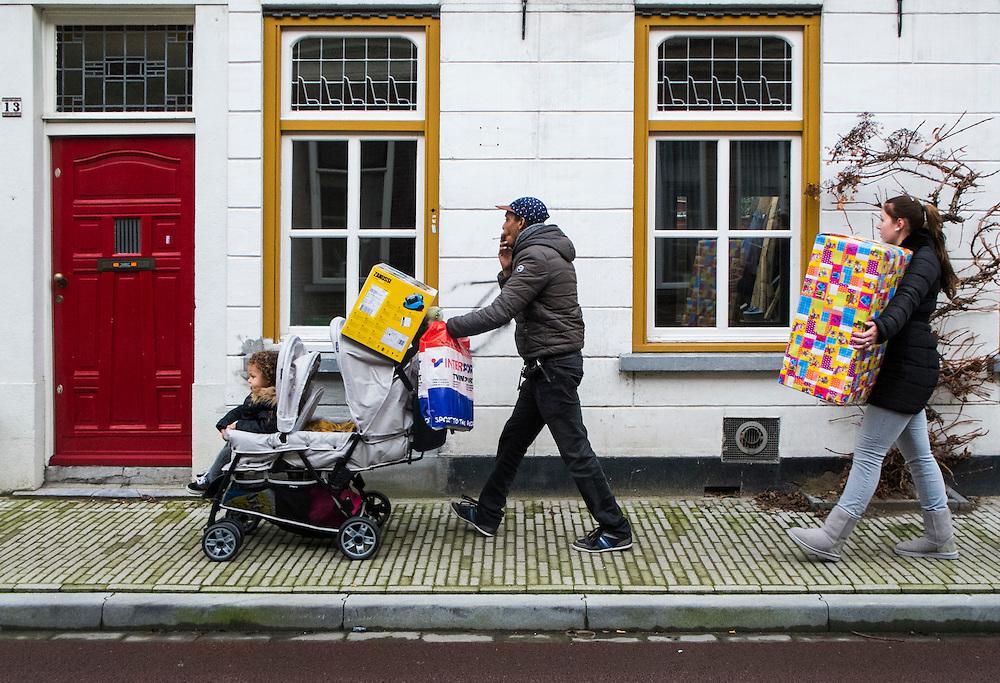 Nederland, Tilburg, 18 jan 2014<br /> Jong gezin keert terug uit de stat met veel gekochte spullen, wellicht voor een verjaardag.<br /> <br /> Foto: Michiel Wijnbergh