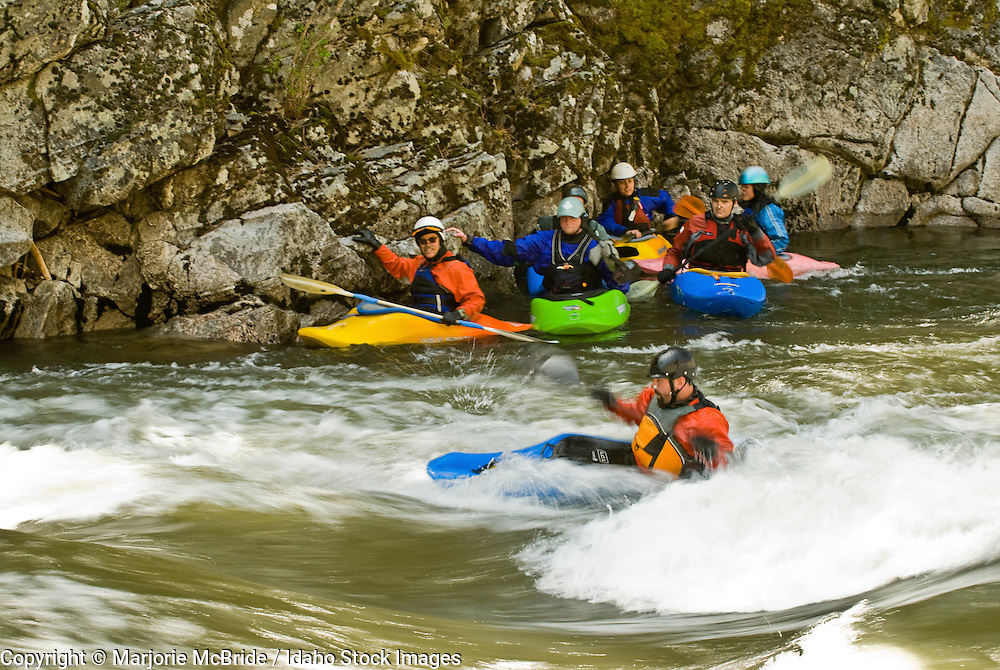 Idaho,  Group of play boaters watch and wait their turn to surf the wave while kayaking the South Fork of the Payette River during spring near Boise, Idaho.