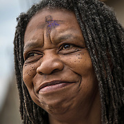 "ALEXANDRIA, VA - MAR1: Diane Jordan, 58, receives ""glitter ashes"" for Ash Wednesday, outside the Braddock Road metro station, in Alexandria, VA, March 1, 2017. Across the country, churches involved with the advocacy group Parity will be giving out ""glitter ashes"" to demonstrate that LGBT people should be included in Christianity.(Photo by Evelyn Hockstein/For The Washington Post)"