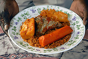 Chez Seneba: Oowner Fallou Sene holds Thiebu Jenn: Djdof rice cooked in a rich tomato sauce served with fish, carrots, cabbage, yucca and eggplant.