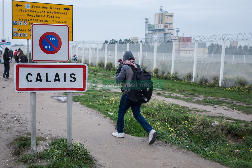 October 24, 2016 - Calais, France - A Migrant passes near the Calais Jungle the town sign of Calais. The refugee camp on the coast to the English Channel is to be cleared today. The approximately 8,000 refugees are distributed after the registration by busses to various reception centers in France. (Credit Image: © Markus Heine/NurPhoto via ZUMA Press)