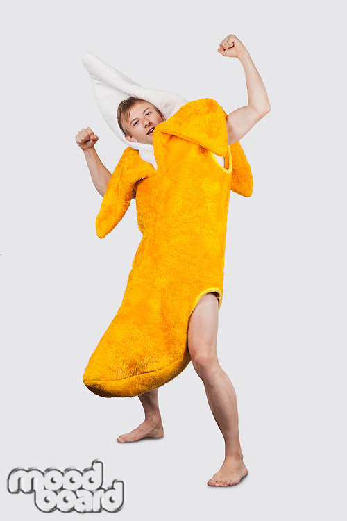 Portrait of young man in banana costume flexing muscle against gray background