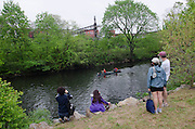 11 May 2013 - Bronx, NY. Spectators watch as a canoe paddles upstream along the Bronx River during the Starlight 5K Canoe Challenge. The 10th annual Bronx River Flotilla is held at the newly-opened Starlight Park in the Bronx. Nearly 200 friends and residents attended the event, which centered around a 5K canoe race up and down the Bronx River. 05/11/2013. Photo credit: ©Skyler Reid