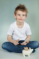 Thoughtful boy with piggy bank and coins over gray background