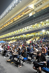 Crowds of spectators in grandstand at horse racing in Happy Valley stadium in Hong Kong