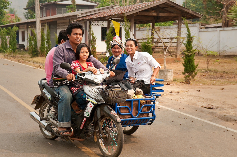 Family riding motorcycle and sidecar through village along the Mae Tang River in rural Chiang Mai Province, Thailand.
