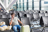 Portrait of man sitting with teddy bear and suit case while waiting for boarding in airport