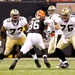 Oct 24, 2010; New Orleans, LA, USA; New Orleans Saints guard Carl Nicks (77) and center Jonathan Goodwin (76) blocks against Cleveland Browns linebacker David Bowens (96) during the first half at the Louisiana Superdome. Mandatory Credit: Derick E. Hingle