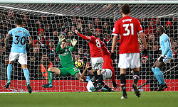 Manchester City goalkeeper Ederson saves a shot on goal by Manchester United's Juan Mata (centre)