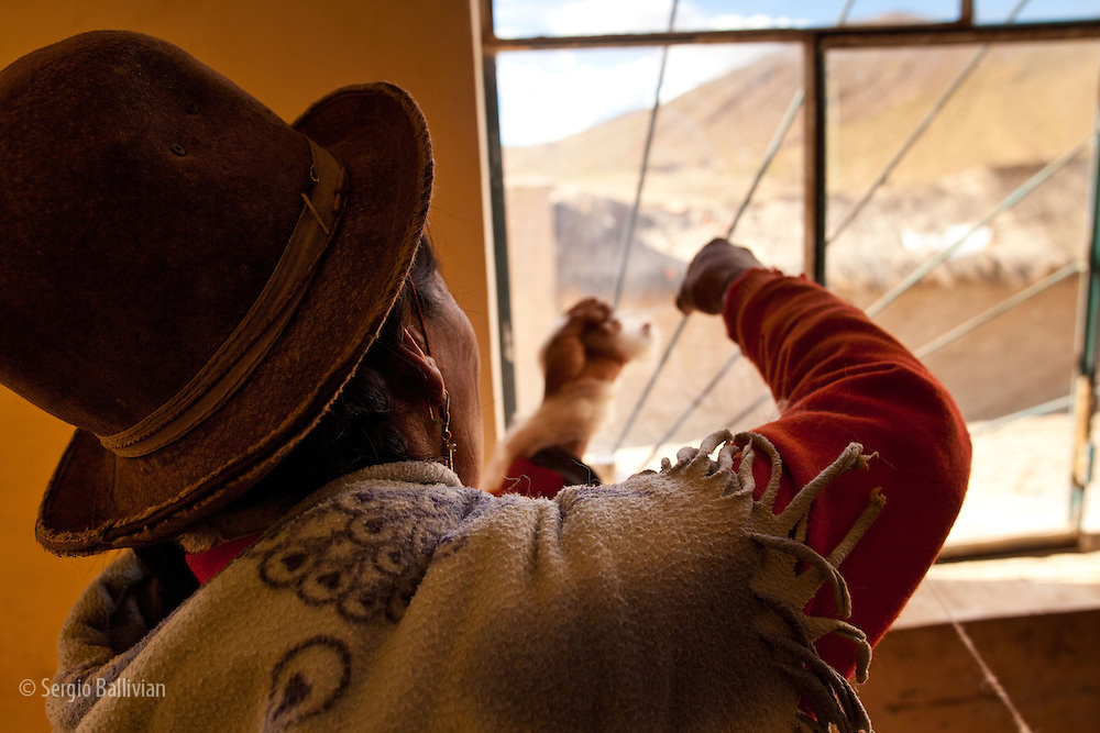 An Aymara woman pulls wool strands apart by hand before making a sweater in southwestern Bolivia's Altiplano.