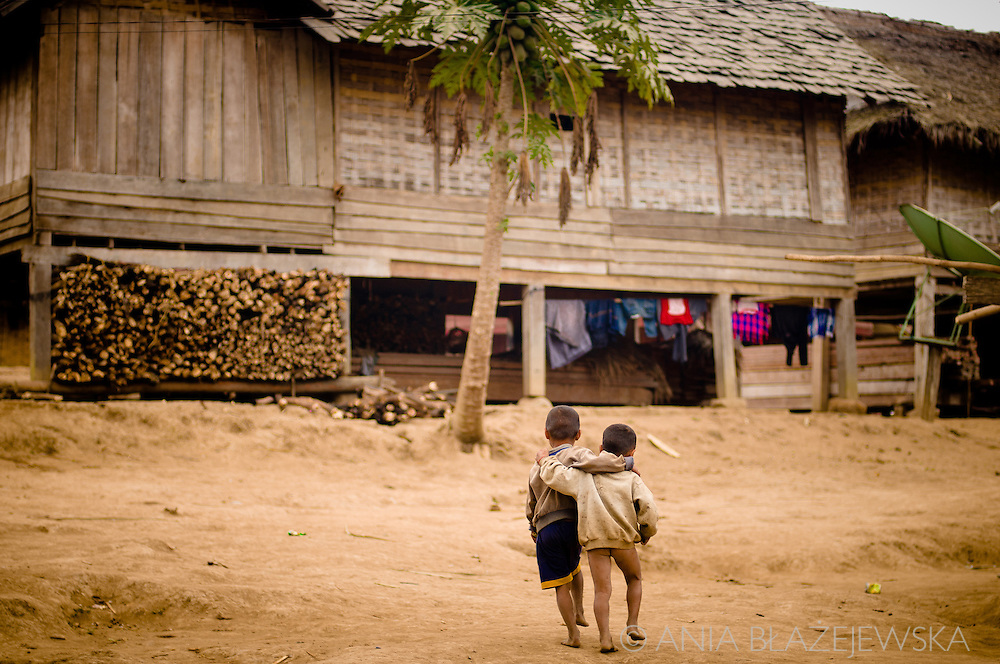 Laos, Luang Nam Tha. Two Khamu boys walking in a Ban Nam Pick village.<br /> <br /> The Khamu arrived in northern Laos and Thailand in the early first millennium AD, making them one of the earliest inhabitants in the region. When the Lao arrived in the area they pushed the Khamu out of the valleys into higher land. <br /> <br /> Traditional Khamu villages can be found in low mountainous areas and forest valleys. The houses are built on low wooden stilts about 1 to 1.5 meters above the ground. The walls are made of bamboo mats without windows, the roof is covered with thatch. Traditional Khamu villages have a communal house, where young adolescent boys live and where men gather for important discussions or to work together on crafts. <br /> <br /> They cultivate rice, maize, cassava, gourds, eggplants, peanuts and vegetables. Besides that Khamu grow tobacco and brew whisky for self-consumption. They keep a few buffaloes, cattle and goats. Pigs and poultry are kept in larger numbers. <br /> <br /> The Khamu believe in several spirits and every village has a guardian spirit. Spirit gates are erected over the entrance to Khamu villages and special houses are built to make sacrifices. The Khamu practice a form of ancestor worship. Every village has a shaman and several sorcerers. <br /> <br /> The Khamu have never engaged intensively in weaving and buy most of their cloths from others. <br /> The festive dress of a Khamu woman includes a long-sleeved dark vest open at the front, often with red hems, a dark based sarong with many colored strings or motifs and a kerchief. On ordinary days Khamu women wear the Lao-styled sarongs and ordinary blouses with a multitude of bright colors. The older women wear a headscarf, the younger women wear their hair bound up in a bun and leave it uncovered. they decorate themselves with silver and copper bracelets can be found on the arms and legs.