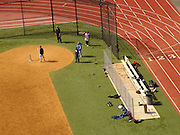 Baseball field and runners track with players seen from above.