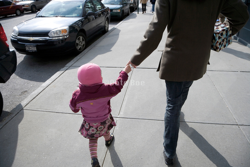 person walking with child on one hand and present under her arm