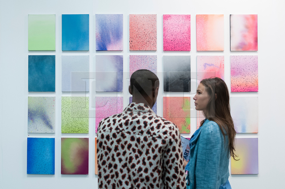 "© Licensed to London News Pictures. 19/05/2016. London, UK. A couple view Zane Lewis's ""Lacquer on Canvas"".  Art16 opens at Olympia, in west London.  Now in its fourth edition, the fair brings together over 100 galleries from more than 30 countries showcasing a diverse cross-section of work by contemporary artists from around the world for buyers and art enthusiasts to visit. Photo credit : Stephen Chung/LNP"
