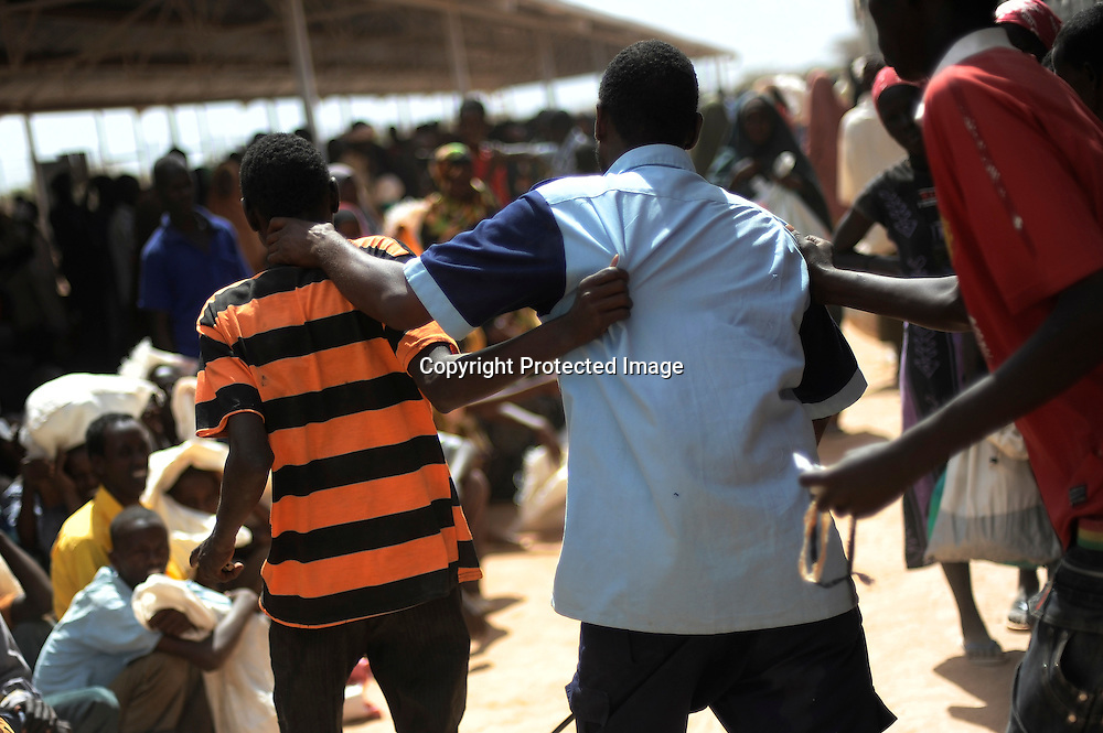 A guard collars a Somali refugee after he tried to jump the line at the World Food Program distribution center in the Ifo settlement at Kenya's Dadaab Refugee Camp, situated northeast of the capital Nairobi near the Somali border, September 2011.