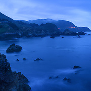 The coastline of Big Sur is seen from a series of cliffs above the swirling seawater after a passing storm at dusk.